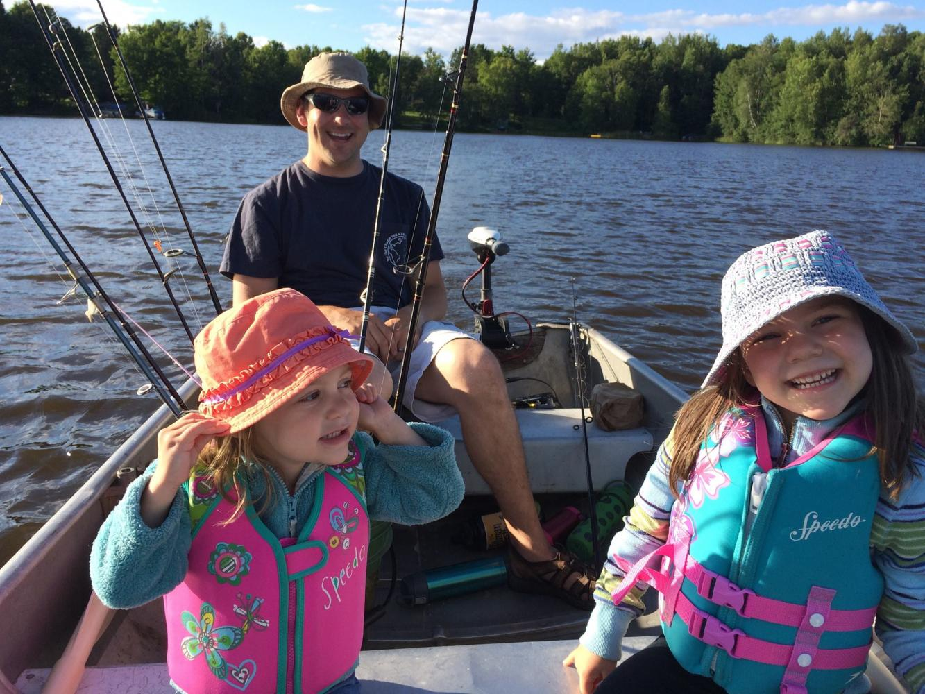 Associative Principal Mr Kevin Formolo cheeses with his two little girls while fishing. Formolo said besides fishing, the girls like to
