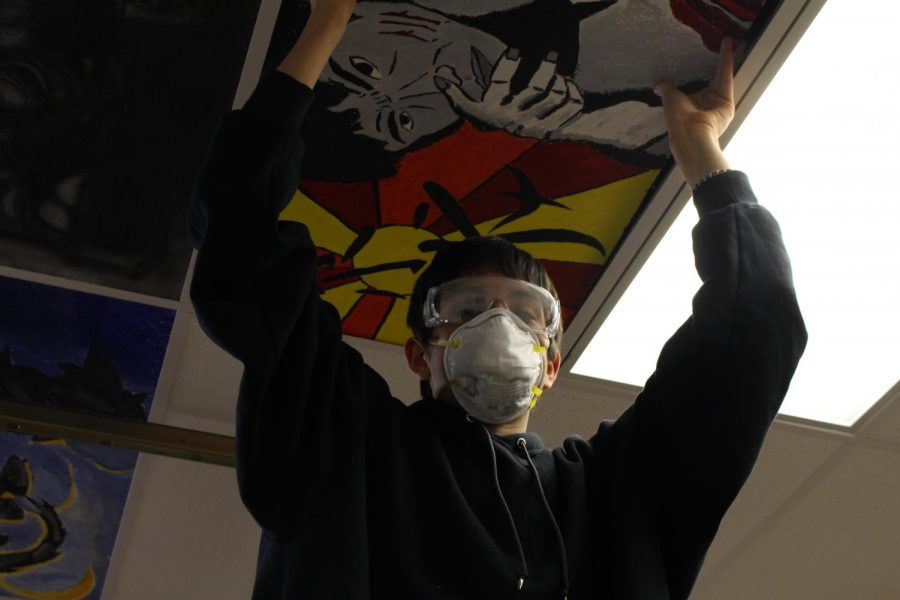 Junior, Nick Gamez, helps place ceiling tiles in the art room.