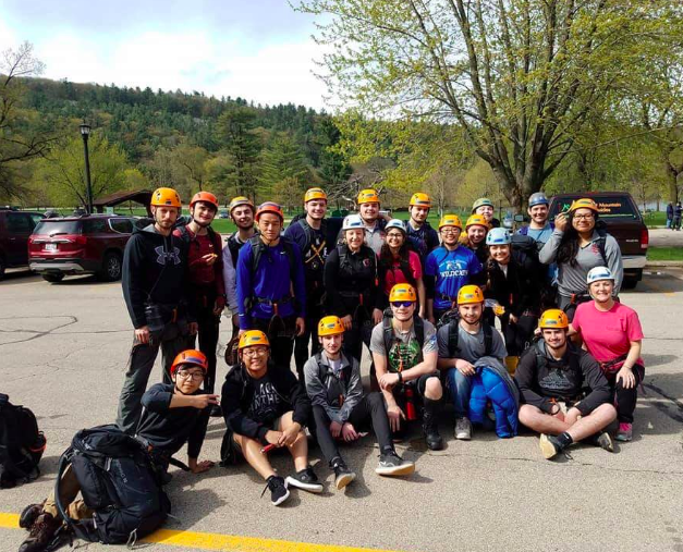 Students and chaperones, pose for a photo while getting ready to go rock climbing. They put this equipment on sponsored by adventure rock.