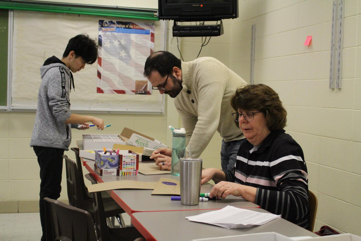Many+teacher+supervisors+lent+a+helping+hand+as+well.+Pictured+here+Mr.+Tachick+and+Ms.+Busche+help+decorate+paper+bags.